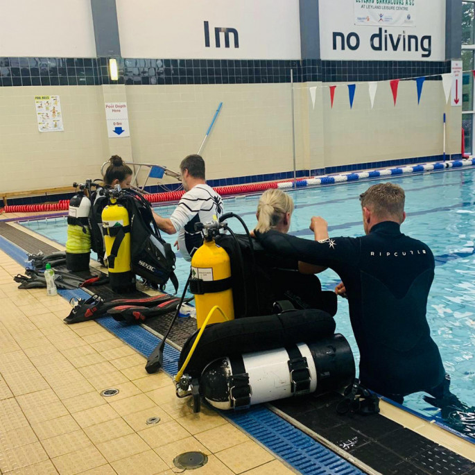 Maddie and Kristine from Northern Diver at a Chorley BSAC Try-Dive session - getting put in to their BCDs